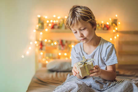 Little boy opens a gift from the advent calendar. Winter seasonal tradition. Christmas advent calendar Фото со стока