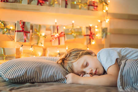 Little blond boy sleeping on a bed and home made advent calendar on a shelf. Winter seasonal tradition. Copy space