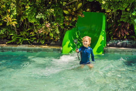 Happy boy on water slide in a swimming pool having fun during summer vacation in a beautiful tropical resort Stock Photo