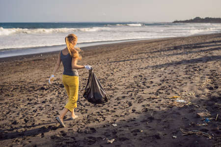 Young woman cleaning up the beach. Natural education of children