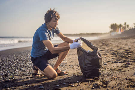 Young man cleaning up the beach. Natural education of children