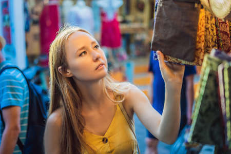 Woman traveler choose souvenirs in the market at Ubud in Bali, Indonesia