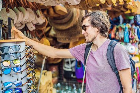 Man traveler choose souvenirs in the market at Ubud in Bali, Indonesia Banco de Imagens