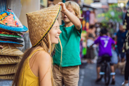 Mom and son travelers choose souvenirs in the market at Ubud in Bali, Indonesia