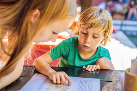 Mother with her son looking at menu in restaurant