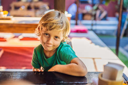 Emotional boy at a table in a cafe. Cute little boy sitting in outdoor restaurant on summer day. child in a cafe waiting for his order