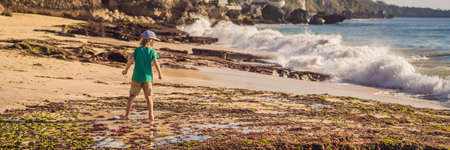 Boy tourist on Pantai Tegal Wangi Beach, Bali Island, Indonesia. Bali Travel Concept. Traveling with children concept. Kids friendly places BANNER, LONG FORMAT