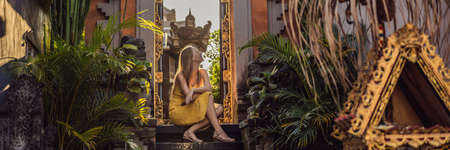 Young woman tourist on the background of Balinese doors. Bali Travel Concept BANNER, LONG FORMAT