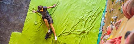 Muscular man practicing rock-climbing on a rock wall indoors BANNER, LONG FORMAT
