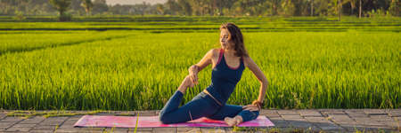 Young woman practice yoga outdoor in rice fields in the morning during wellness retreat in Bali BANNER, LONG FORMAT Banco de Imagens