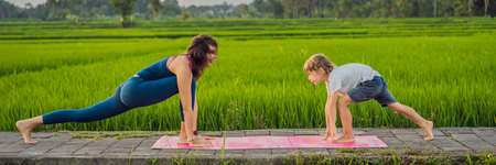 Boy and his yoga teacher doing yoga in a rice field BANNER, LONG FORMAT