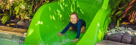 Happy boy on water slide in a swimming pool having fun during summer vacation in a beautiful tropical resort BANNER, LONG FORMAT