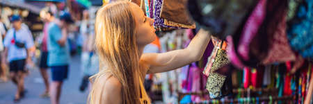Woman traveler choose souvenirs in the market at Ubud in Bali, Indonesia BANNER, LONG FORMAT Banco de Imagens