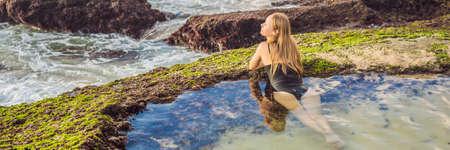 Young woman tourist on Pantai Tegal Wangi Beach sitting in a bath of sea water, Bali Island, Indonesia. Bali Travel Concept BANNER, LONG FORMAT