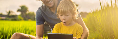 Dad and son sitting on the field holding tablet. Boy sitting on the grass on sunny day. Home schooling or playing a tablet BANNER, LONG FORMAT