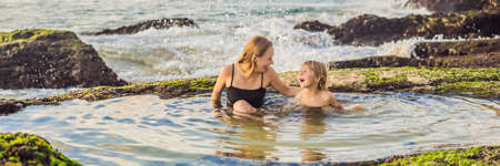 BANNER, LONG FORMAT Mother and son tourists on Pantai Tegal Wangi Beach sitting in a bath of sea water, Bali Island, Indonesia. Bali Travel Concept. Traveling with children concept. Kids friendly places