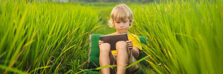 Happy child sitting on the field holding tablet. Boy sitting on the grass on sunny day. Home schooling or playing a tablet BANNER, LONG FORMAT Stockfoto