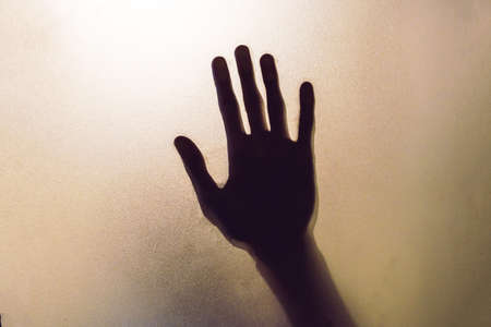 The shadow hands of human behind the glass