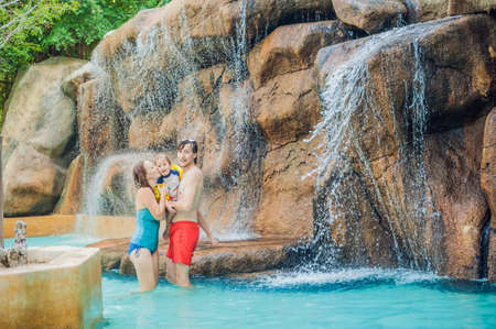 Happy family mother, father and son relaxing under a waterfall in aquapark