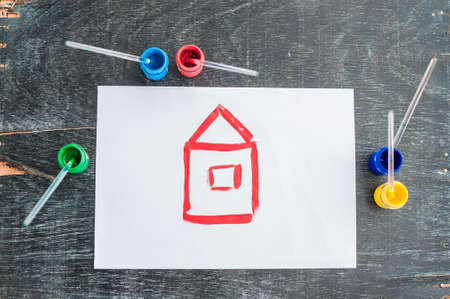 Childrens drawing of a house painted with colored paints. Home concept