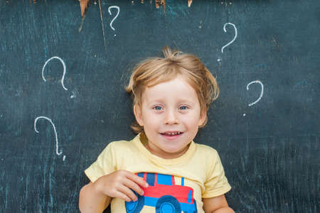 Top view of a little blond kid boy with question mark on blackboard Stock Photo