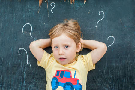 Top view of a little blond kid boy with question mark on blackboard.