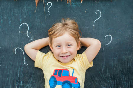 Top view of a little blond kid boy with question mark on blackboard. Concept for confusion, brainstorming and choice Stock Photo