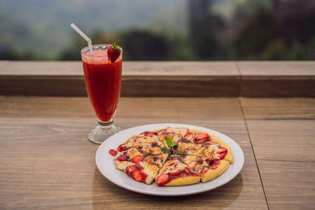 Delicious strawberry pizza on a balinese tropical nature background. Bali island, Indonesia