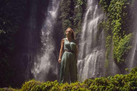 Frau im türkisfarbenen Kleid an den Sekumpul-Wasserfällen im Dschungel auf der Insel Bali, Indonesien. Bali Reisekonzept