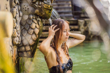Young woman in hot springs banjar. Thermal water is released from the mouth of statues at a hot springs in Banjar, Bali, Indonesia