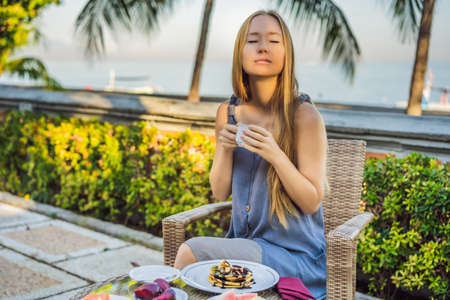 Young woman having romantic breakfast in sunrise at resort restaurant outdoor. Healthy food drink for breakfast. Beautiful woman at vacation