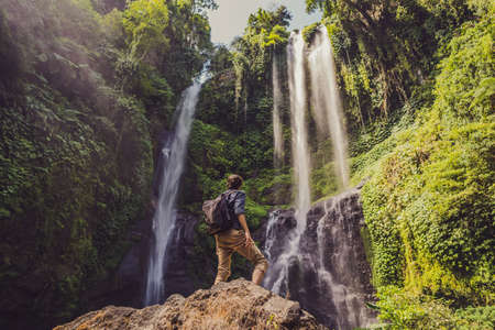 Man in turquoise dress at the Sekumpul waterfalls in jungles on Bali island, Indonesia. Bali Travel Concept.
