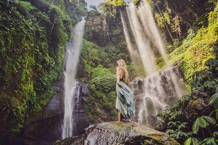 Woman in turquoise dress at the Sekumpul waterfalls in jungles on Bali island, Indonesia. Bali Travel Concept. Banco de Imagens