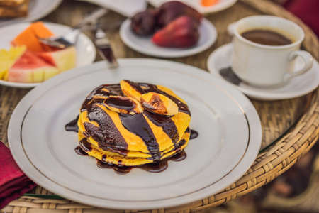 Pancakes with banana and chocolate for breakfast.