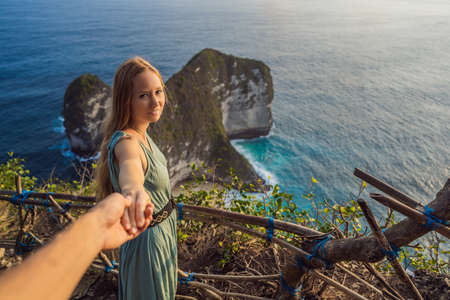 Family vacation lifestyle. Happy woman stand at viewpoint. Look at beautiful beach under high cliff. Travel destination in Bali. Popular place to visit on Nusa Penida island Stock Photo