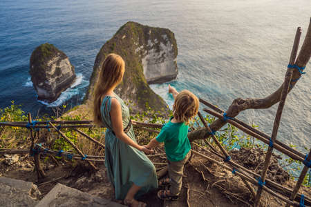 Family vacation lifestyle. Happy mother and son stand at viewpoint. Look at beautiful beach under high cliff. Travel destination in Bali. Popular place to visit on Nusa Penida island. Reklamní fotografie - 132225318