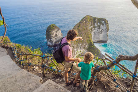 Family vacation lifestyle. Happy father and son stand at viewpoint. Look at beautiful beach under high cliff. Travel destination in Bali. Popular place to visit on Nusa Penida island. 版權商用圖片