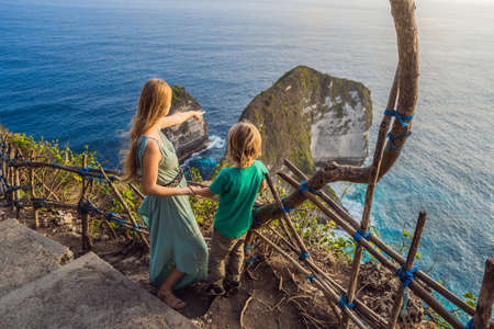 Family vacation lifestyle. Happy mother and son stand at viewpoint. Look at beautiful beach under high cliff. Travel destination in Bali. Popular place to visit on Nusa Penida island.