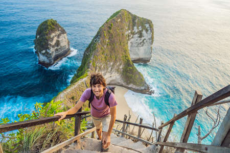 Family vacation lifestyle. Happy man stand at viewpoint. Look at beautiful beach under high cliff. Travel destination in Bali. Popular place to visit on Nusa Penida island