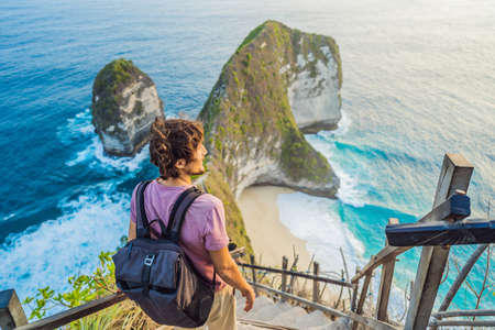 Family vacation lifestyle. Happy man stand at viewpoint. Look at beautiful beach under high cliff. Travel destination in Bali. Popular place to visit on Nusa Penida island.