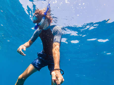 Man with mask snorkeling in clear water.