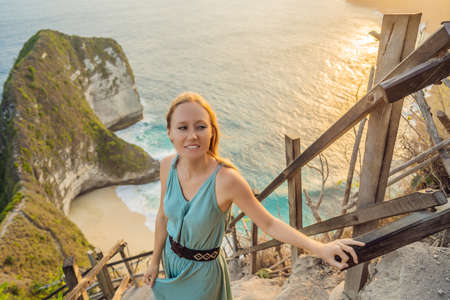 Family vacation lifestyle. Happy woman stand at viewpoint. Look at beautiful beach under high cliff. Travel destination in Bali. Popular place to visit on Nusa Penida island Фото со стока
