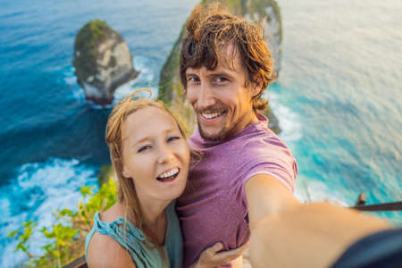 Family vacation lifestyle. Happy couple - man and woman stand at viewpoint. Look at beautiful beach under high cliff. Travel destination in Bali. Popular place to visit on Nusa Penida island