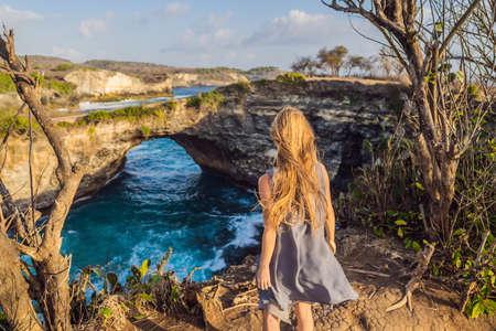 Young woman tourist near Broken Beach in Nusa Penida, Indonesia Angels BillaBong Beach. Popular tourist destination Bali
