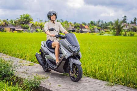 Male traveler on a bike among a rice field. Tourist travels to Bali