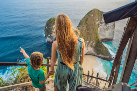 Family vacation lifestyle. Happy mother and son stand at viewpoint. Look at beautiful beach under high cliff. Travel destination in Bali. Popular place to visit on Nusa Penida island Фото со стока