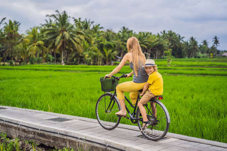 Mother and son ride a bicycle on a rice field in Ubud, Bali.