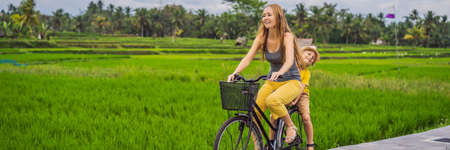 Mother and son ride a bicycle on a rice field in Ubud, Bali