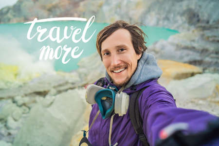TRAVEL MORE concept Young man tourist makes a selfie standing at the edge of the crater of the Ijen volcano or Kawah Ijen on the Indonesian language. Famous volcano containing the biggest in the world acid lake and sulfur mining spot at the place where volcanic gasses come from the volcano Imagens
