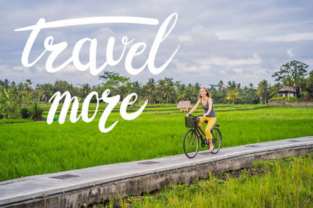 TRAVEL MORE concept A young woman rides a bicycle on a rice field in Ubud, Bali. Bali Travel Concept. Stock fotó